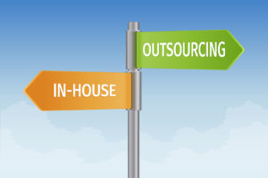 signpost showing options in-house or outsourcing